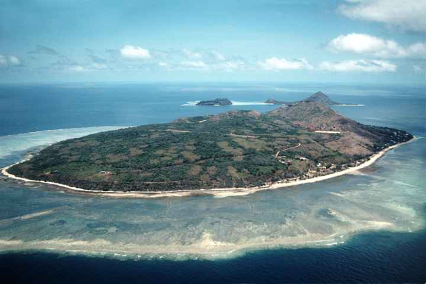 Mer or Murray Island and the smaller islands of Dawar and Waier behind it, in the eastern Torres Strait Islands. The island is a high rocky island with the reef around it clearly visible.